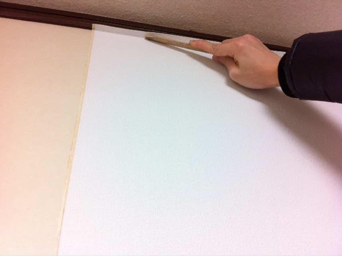 竹べらで壁紙の端部分に折り目をつける