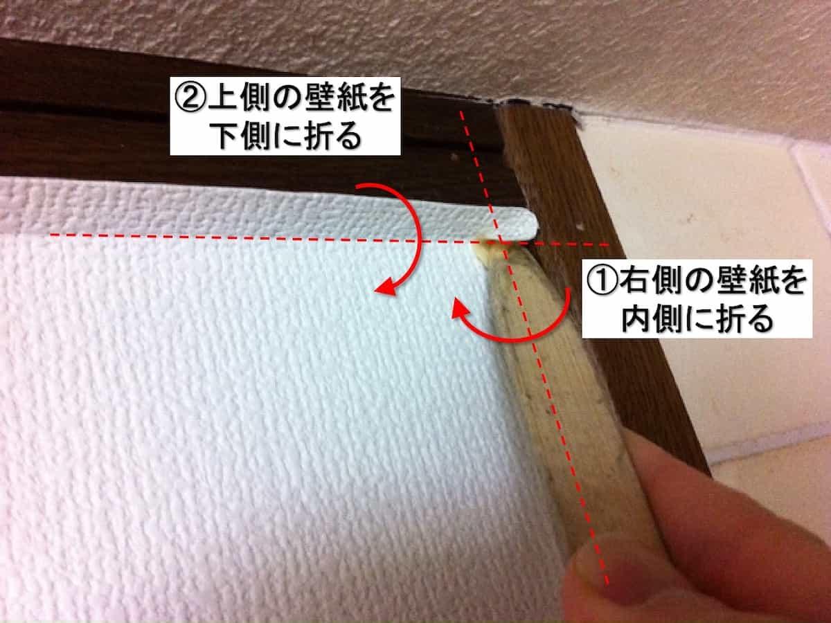 竹べらで角部分の折り目を壁紙につけている様子