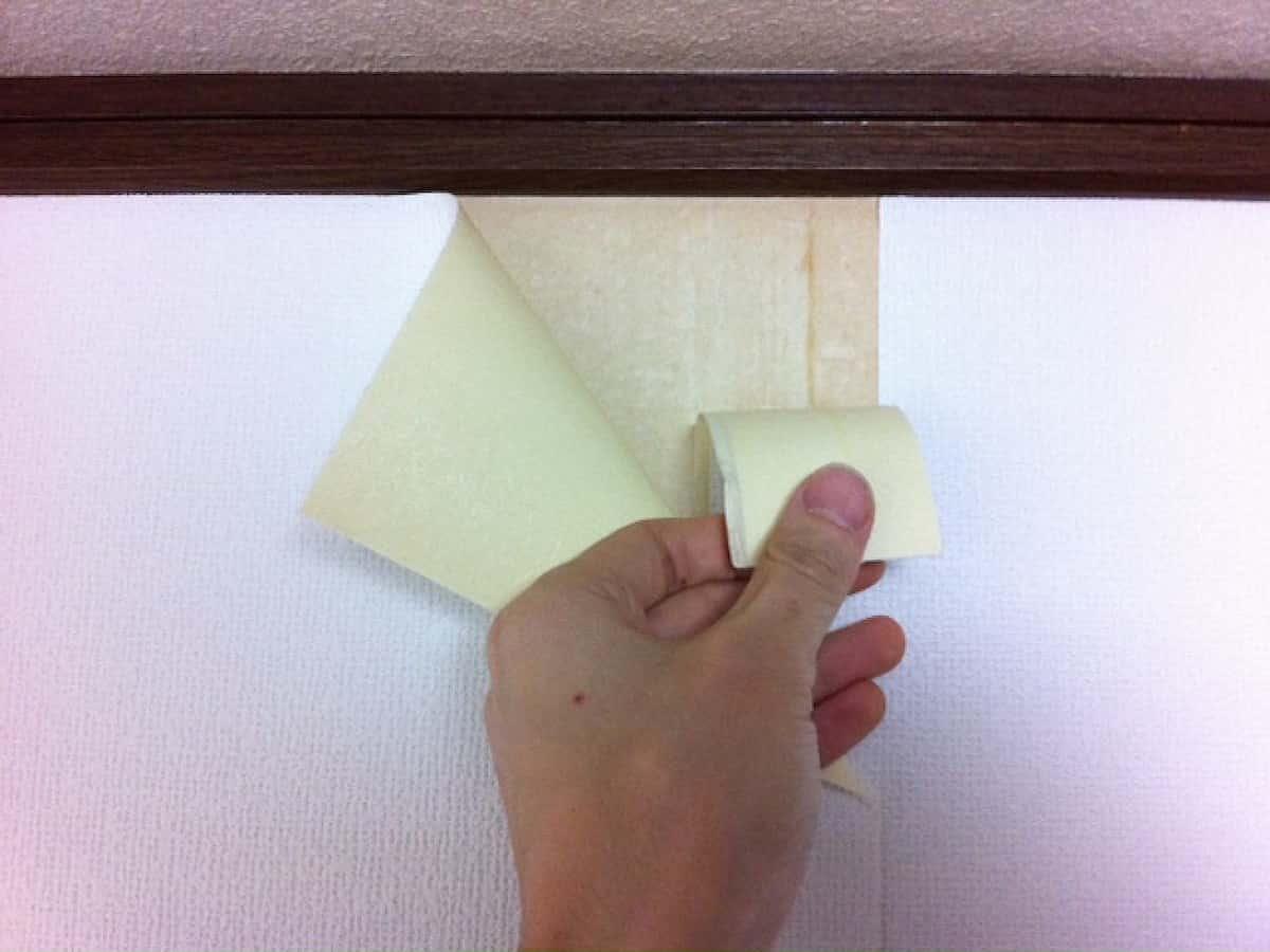裏側に重なった不要な壁紙を剥がす様子