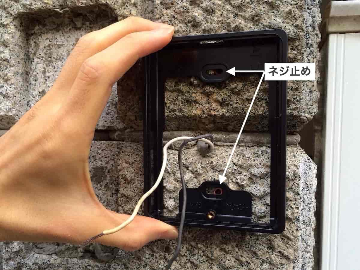 インターホンの屋外カメラの土台部品をブロック塀にネジ止めする様子
