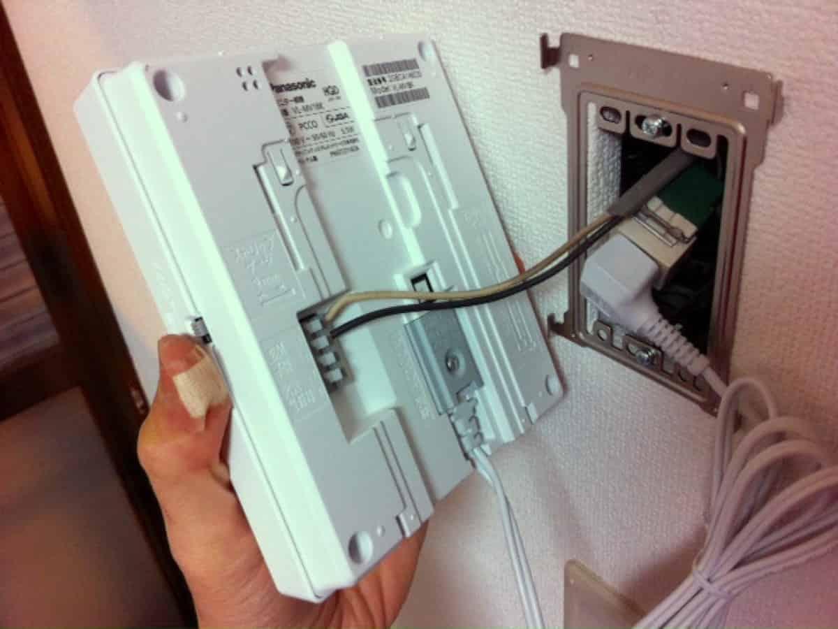 室内モニターのプラグを電源コンセントに差し込む様子