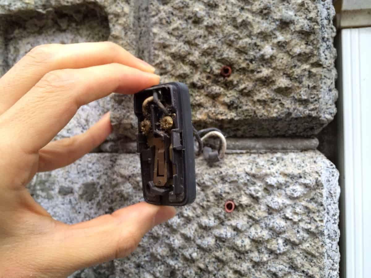インターホン交換のために屋外の古い呼び出しベルを取り外す様子