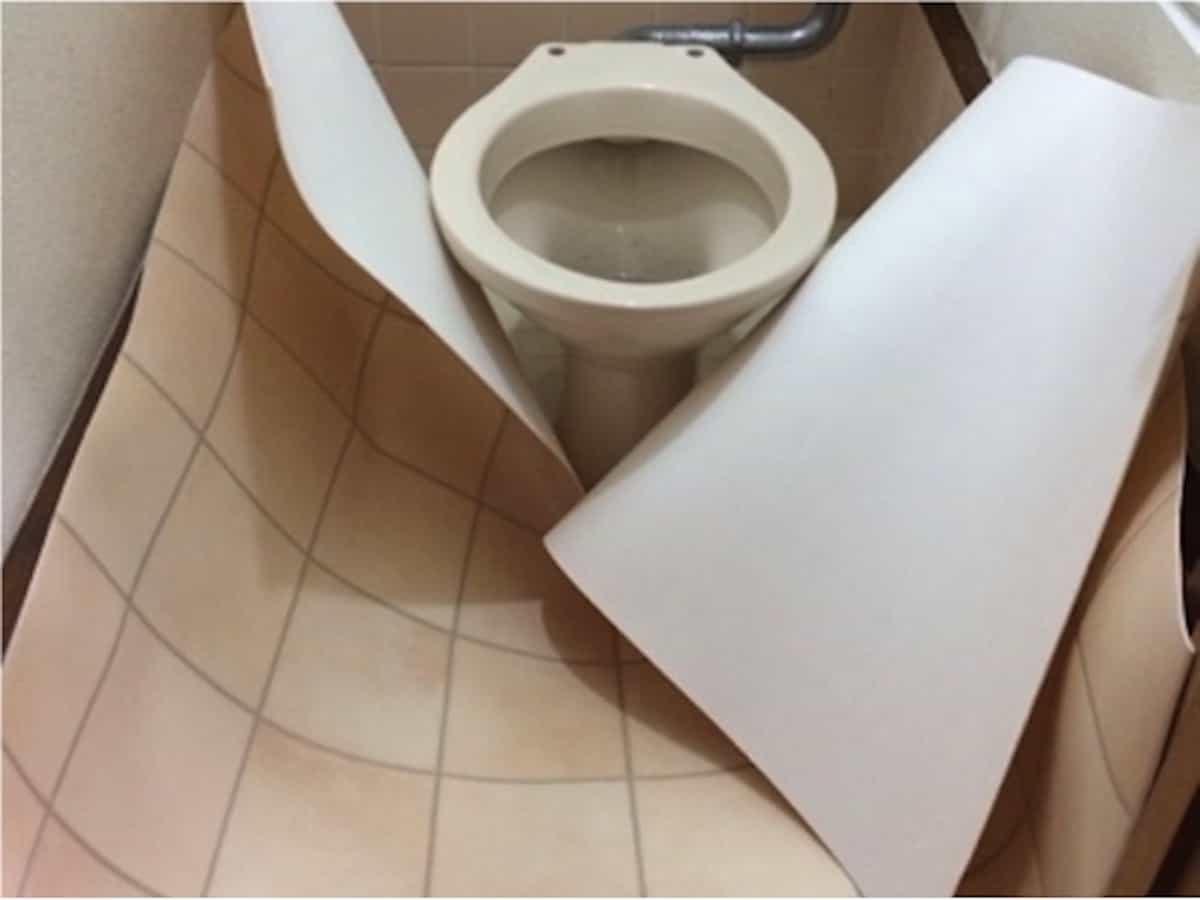 カットしたクッションフロアをトイレに広げる様子