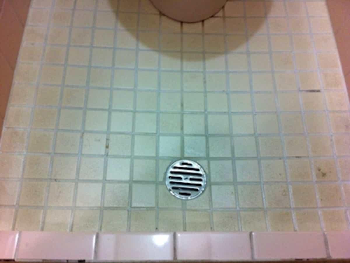 DIYでクッションフロアを貼る前のトイレのタイル床の排水口