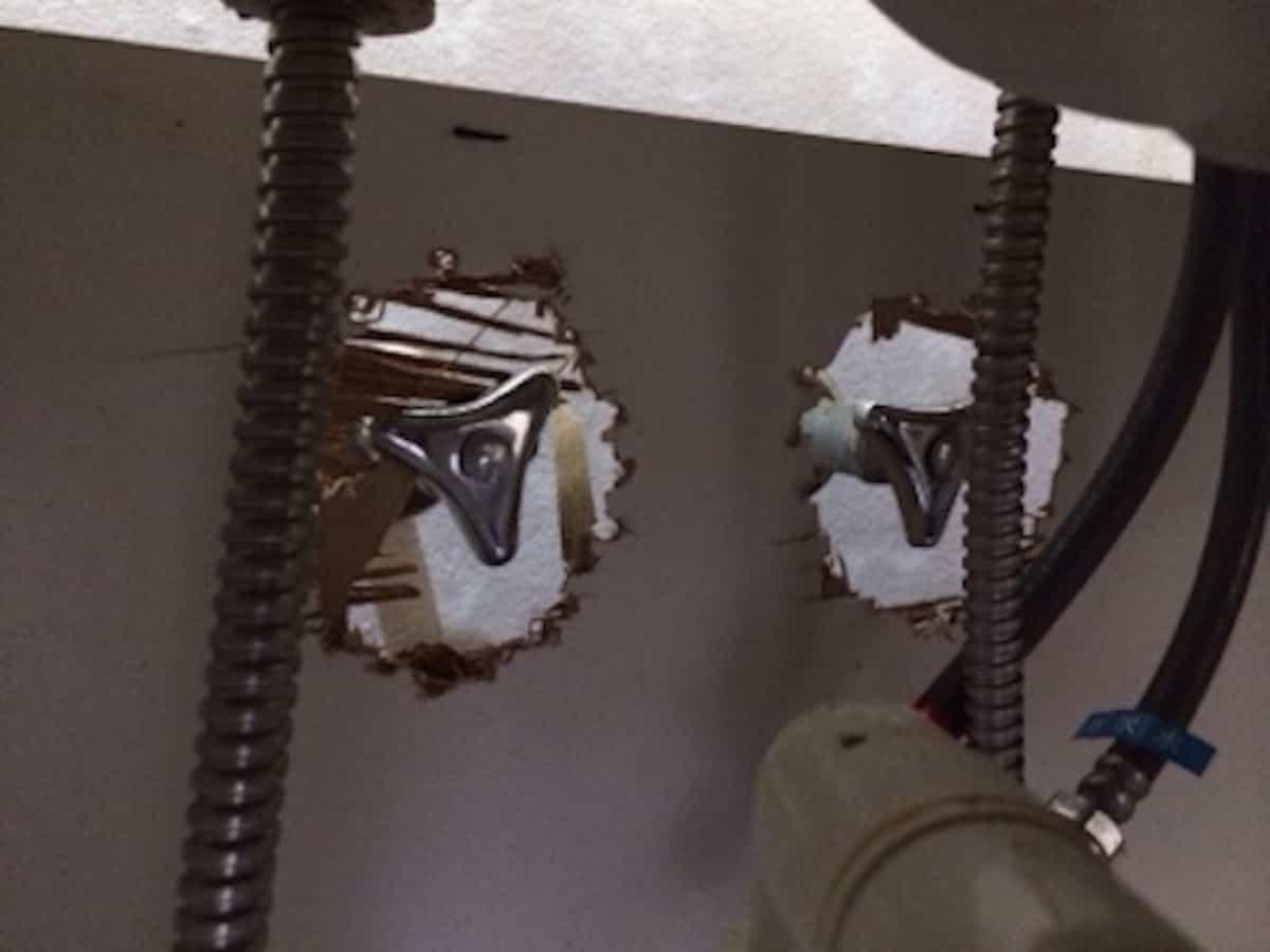 壁の給水栓まわりの板に穴あけした様子