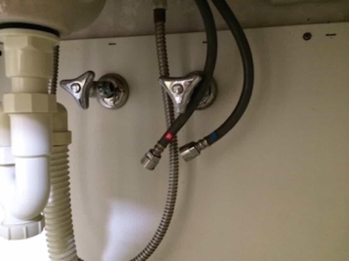 洗面台の給水ホースを壁の給水栓から取り外した様子