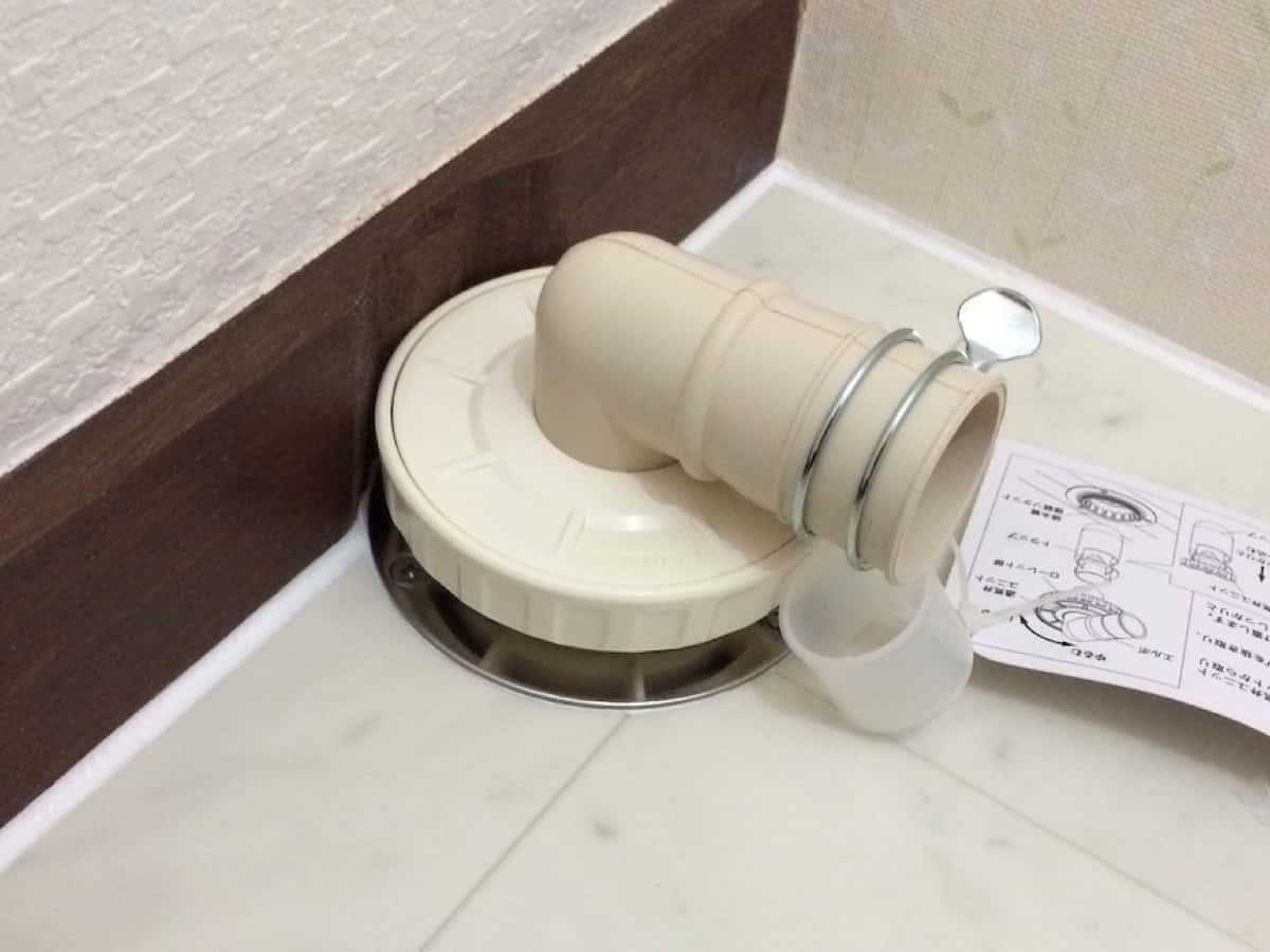 床に穴だけあいた排水口から出てくる下水のにおいを防ぐカクダイの洗濯機用排水トラップを取り付けた様子