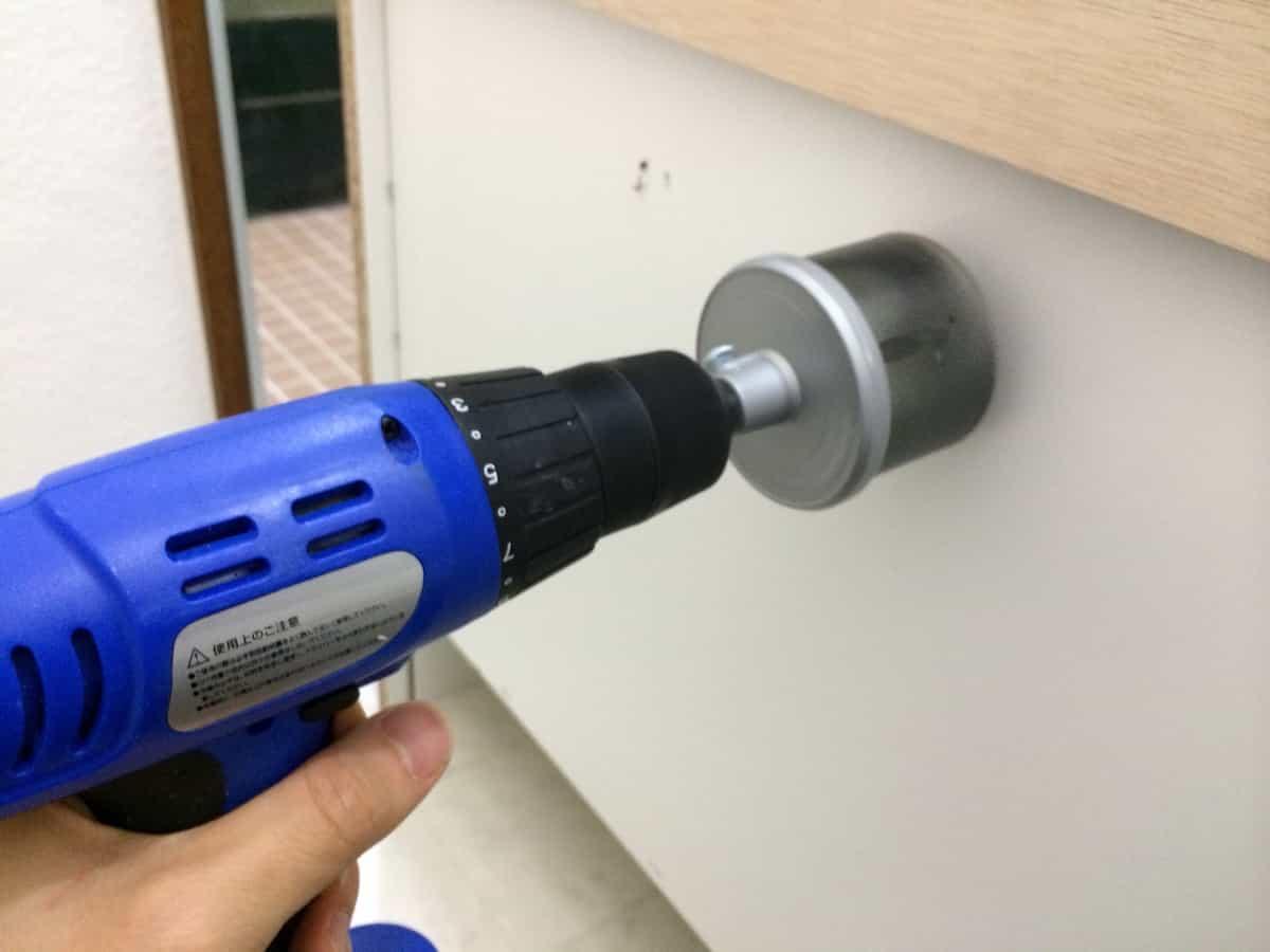 ホールソーで洗面化粧台の背面に給水栓用の穴をあける様子