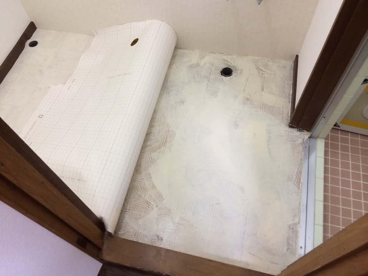 洗面所の床に新しいクッションフロア(CF・床シート)を貼る様子