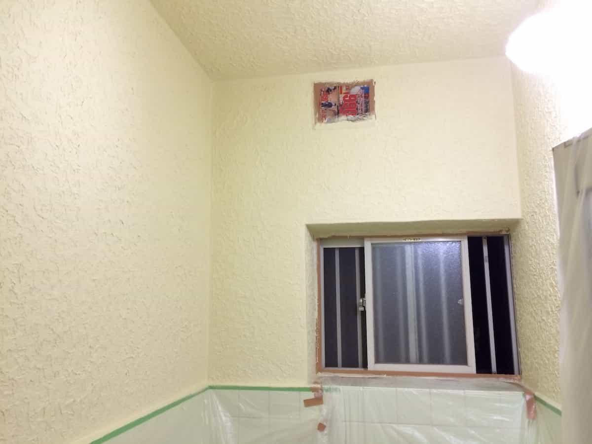 浴室のモルタル(コンクリート)壁の側面を塗装する様子