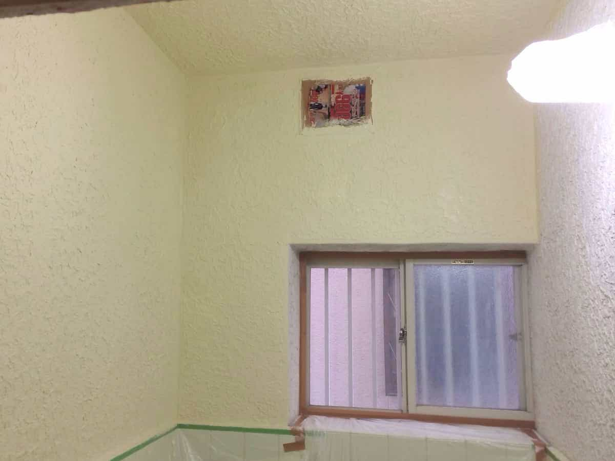浴室のモルタル壁の側面にペンキ塗装している様子