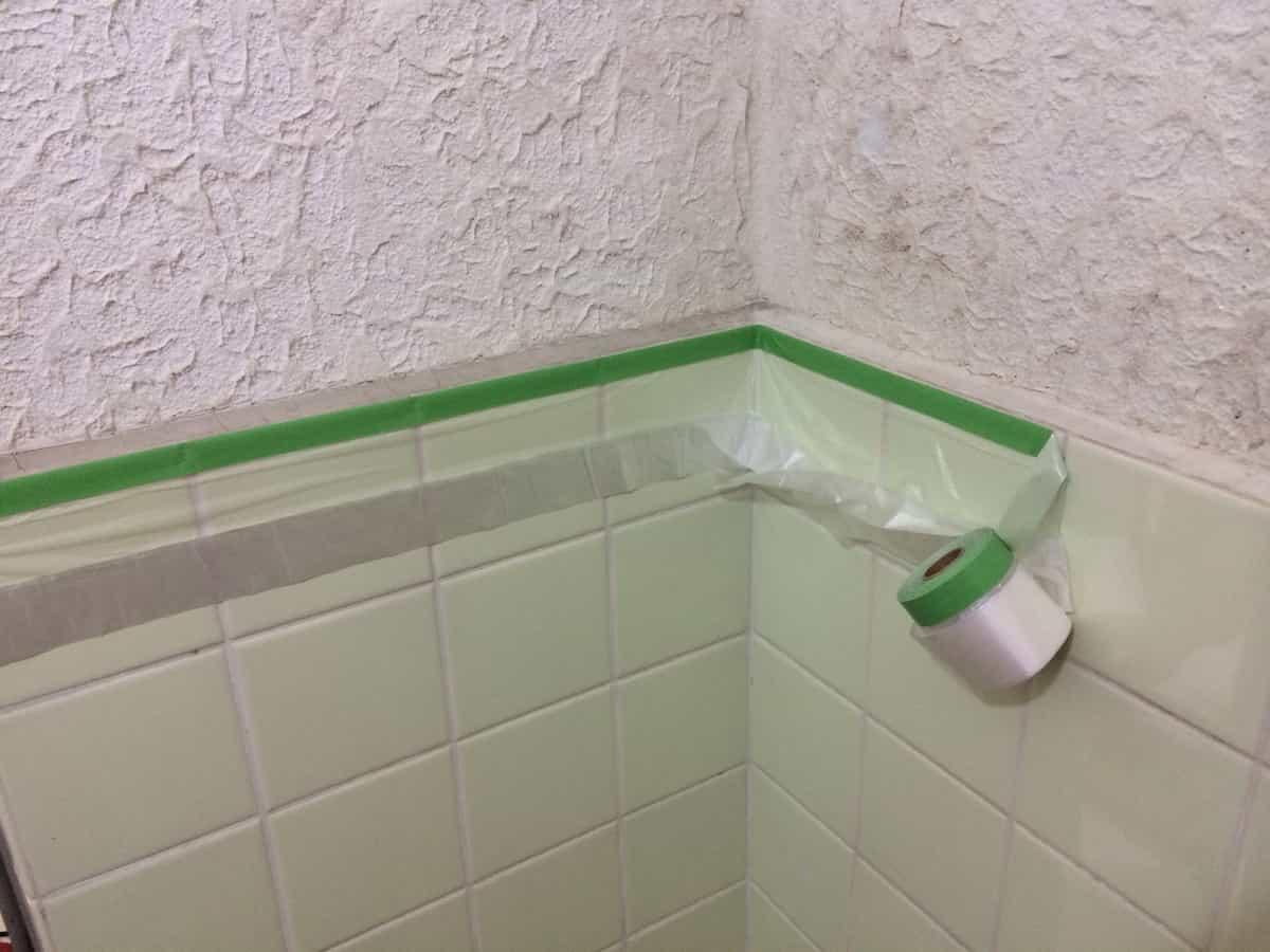 浴室のモルタル壁を塗装する前に養生シートで養生する様子