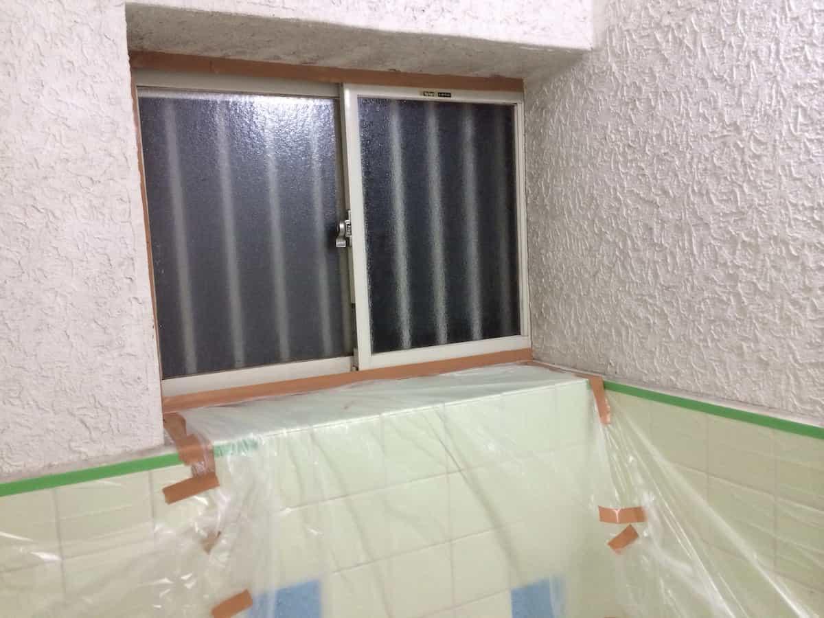 浴室のモルタル壁を塗装する前にマスキングテープで養生する様子