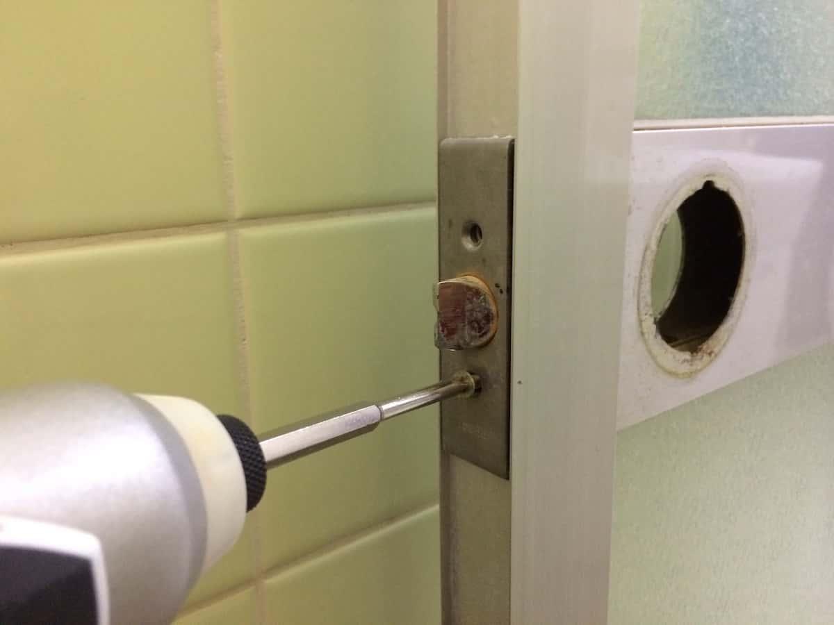 浴室扉の横のラッチを分解する様子