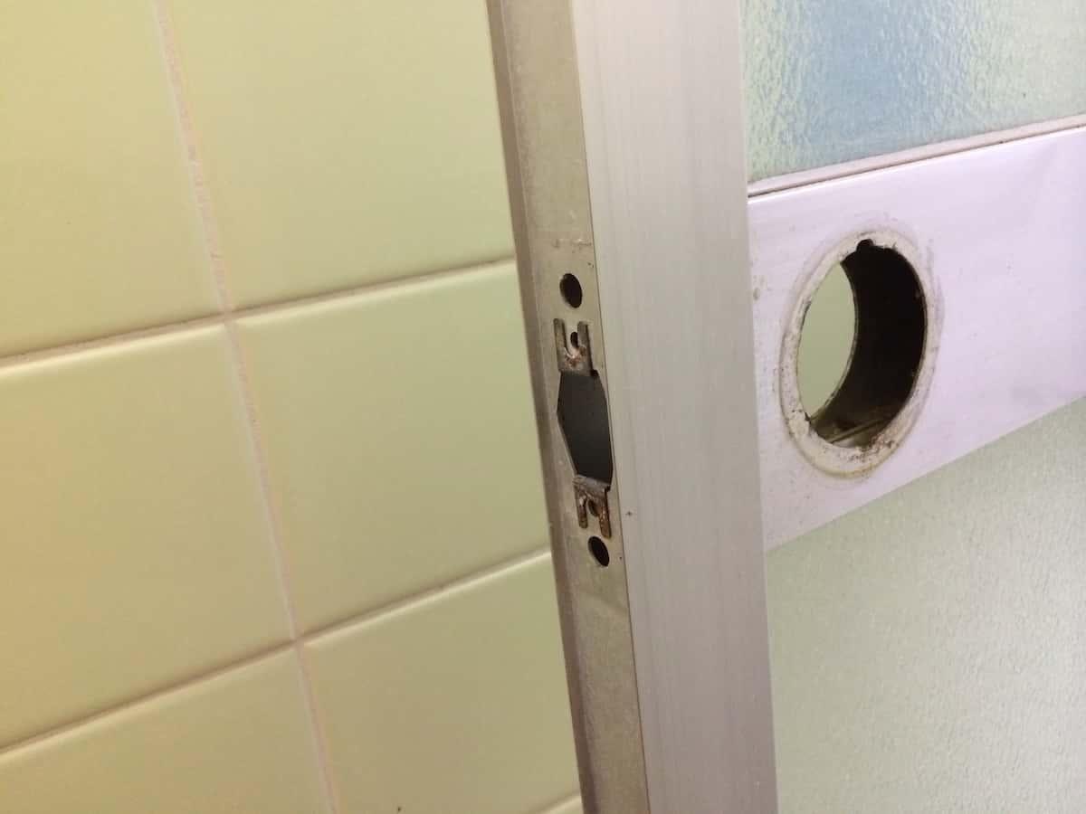 ネジ穴のない浴室扉のドアノブを取り外した様子