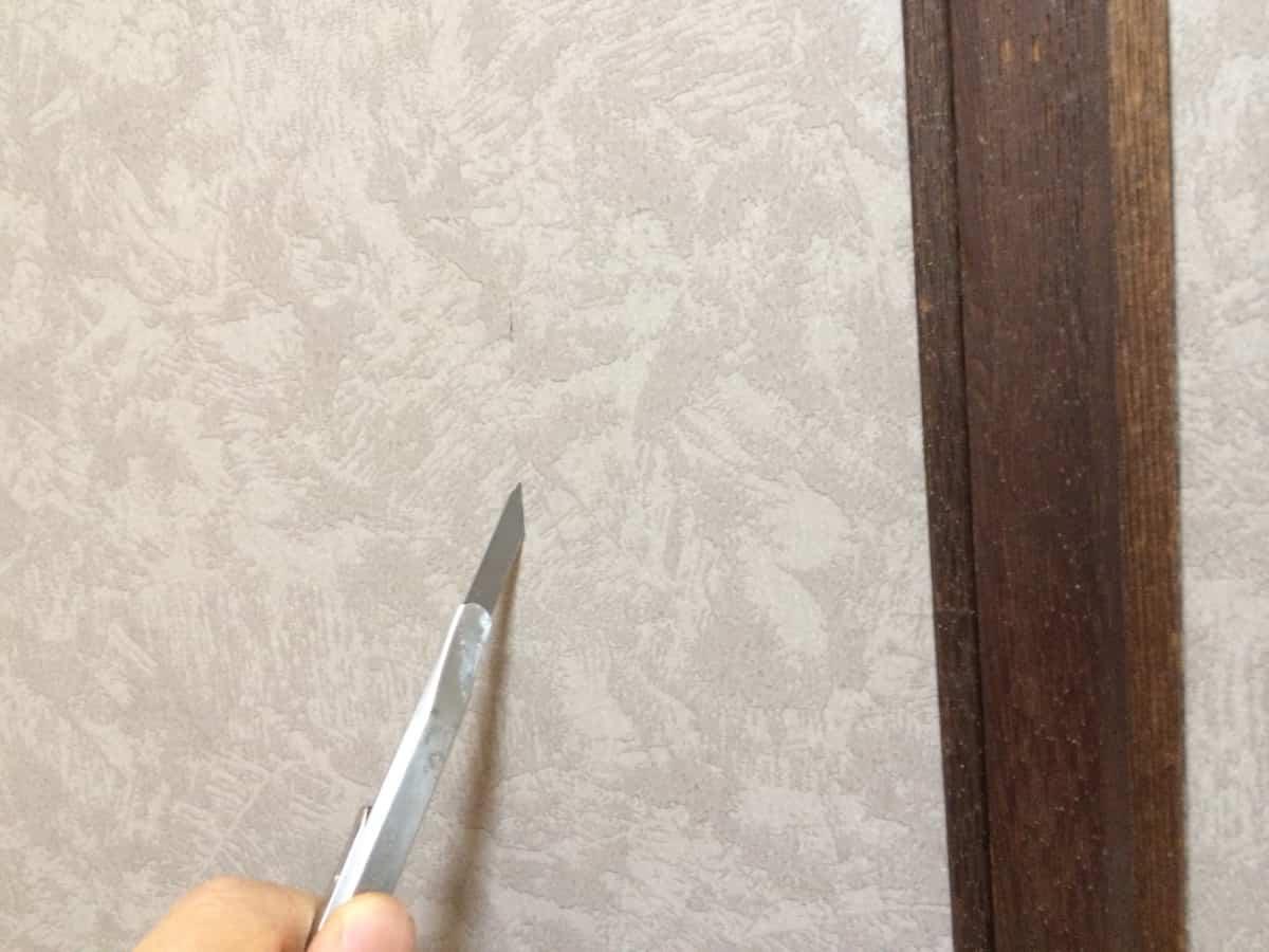 引き手取り付け部分のふすま紙にカッターで切れ込みを入れる