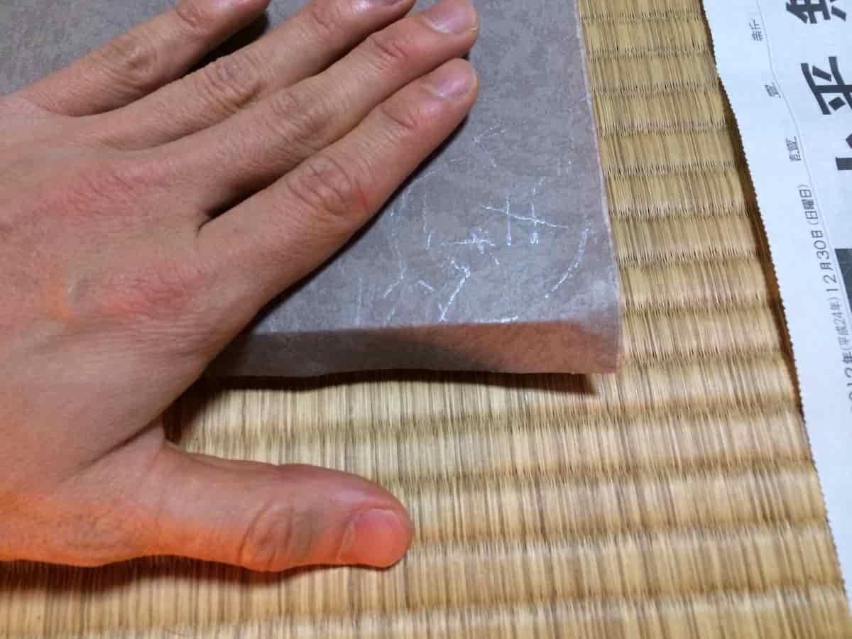 糊付けしたふすま紙ののりしろ部分を折り込む様子