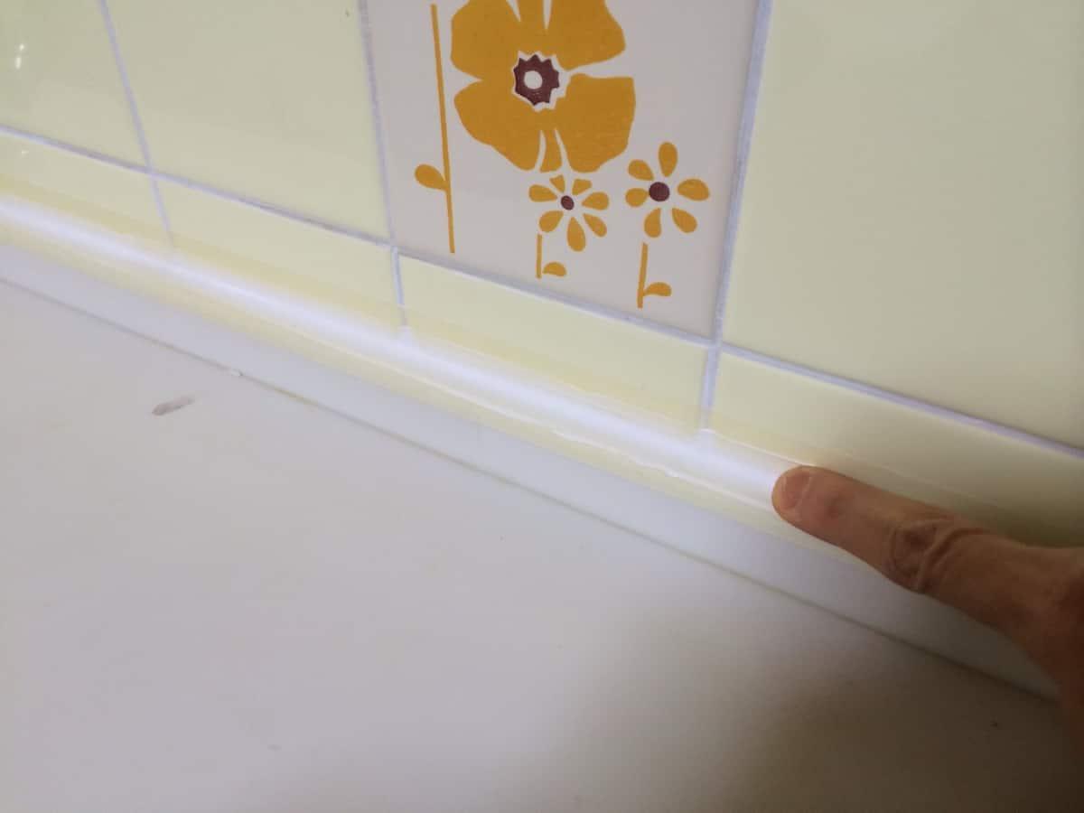 キッチンと壁の隙間に注入したシリコンを指でならす