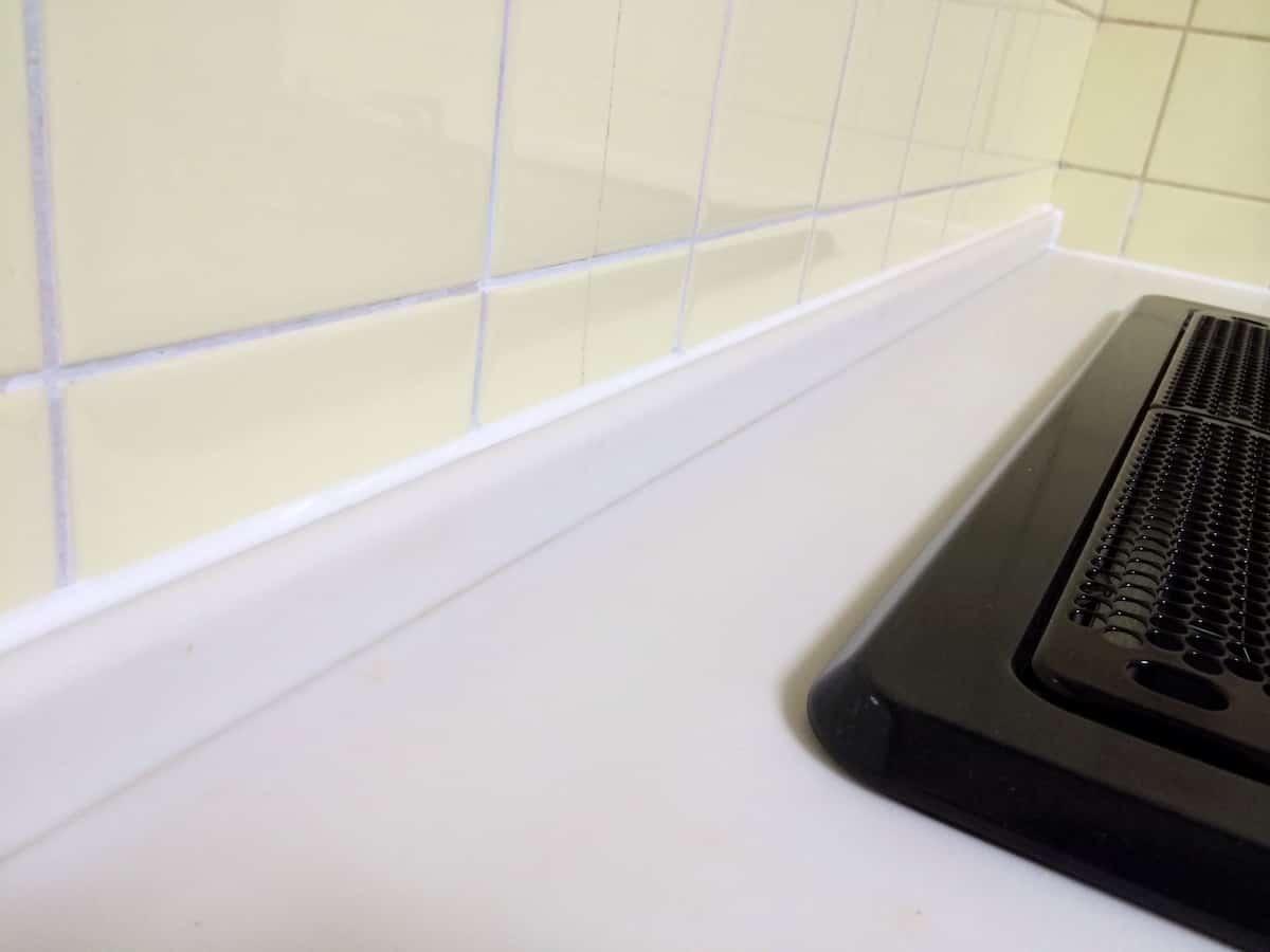 キッチンと壁の隙間をシリコンコーキングできれいに打ち直した様子