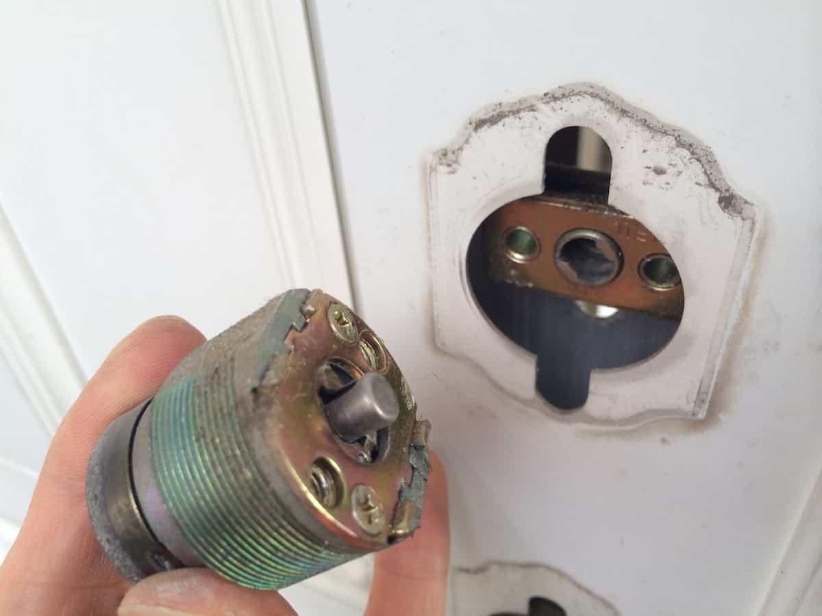玄関扉の古い鍵シリンダーを取り外した様子