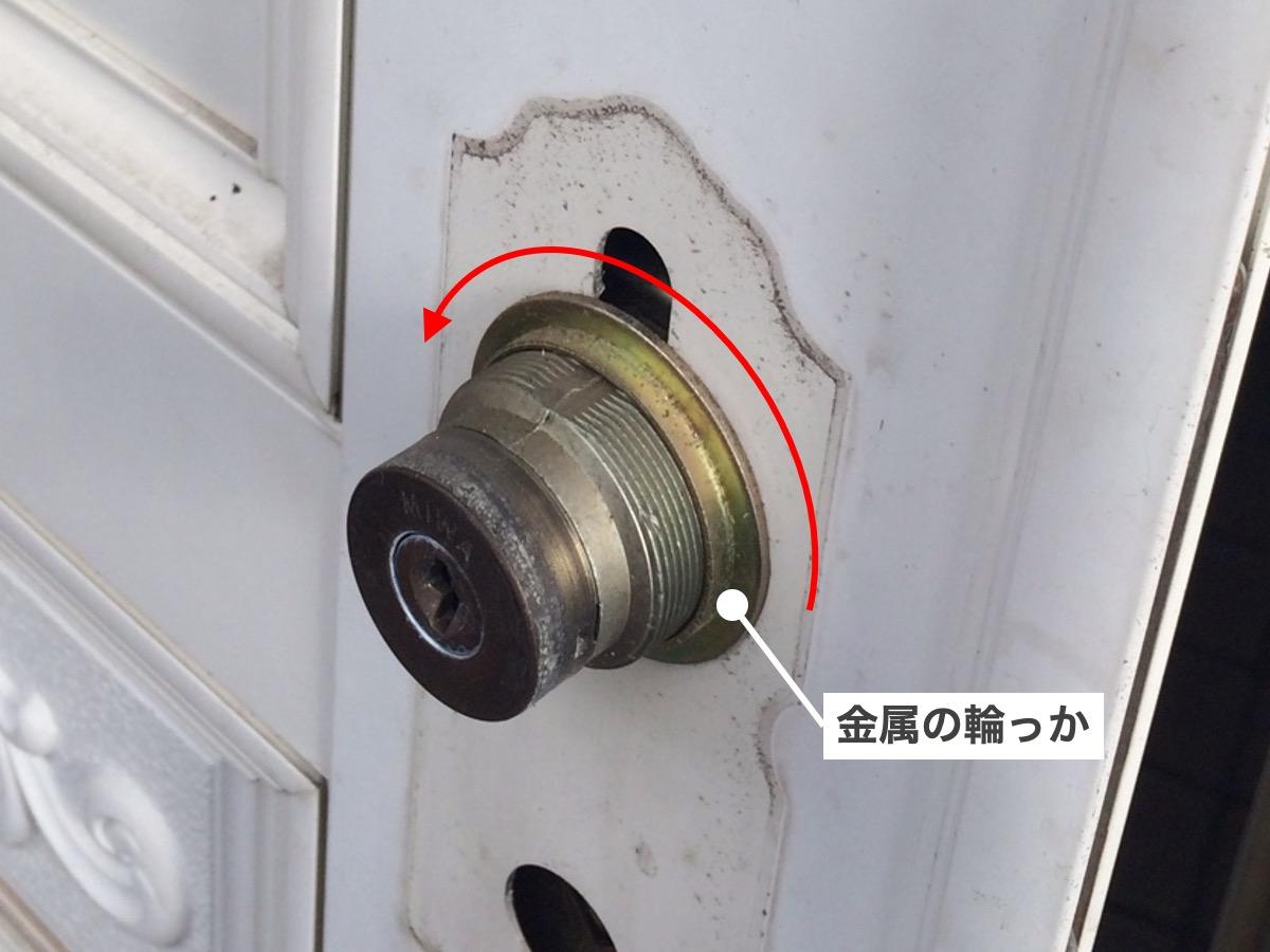 玄関扉の古いドアシリンダーを分解する様子