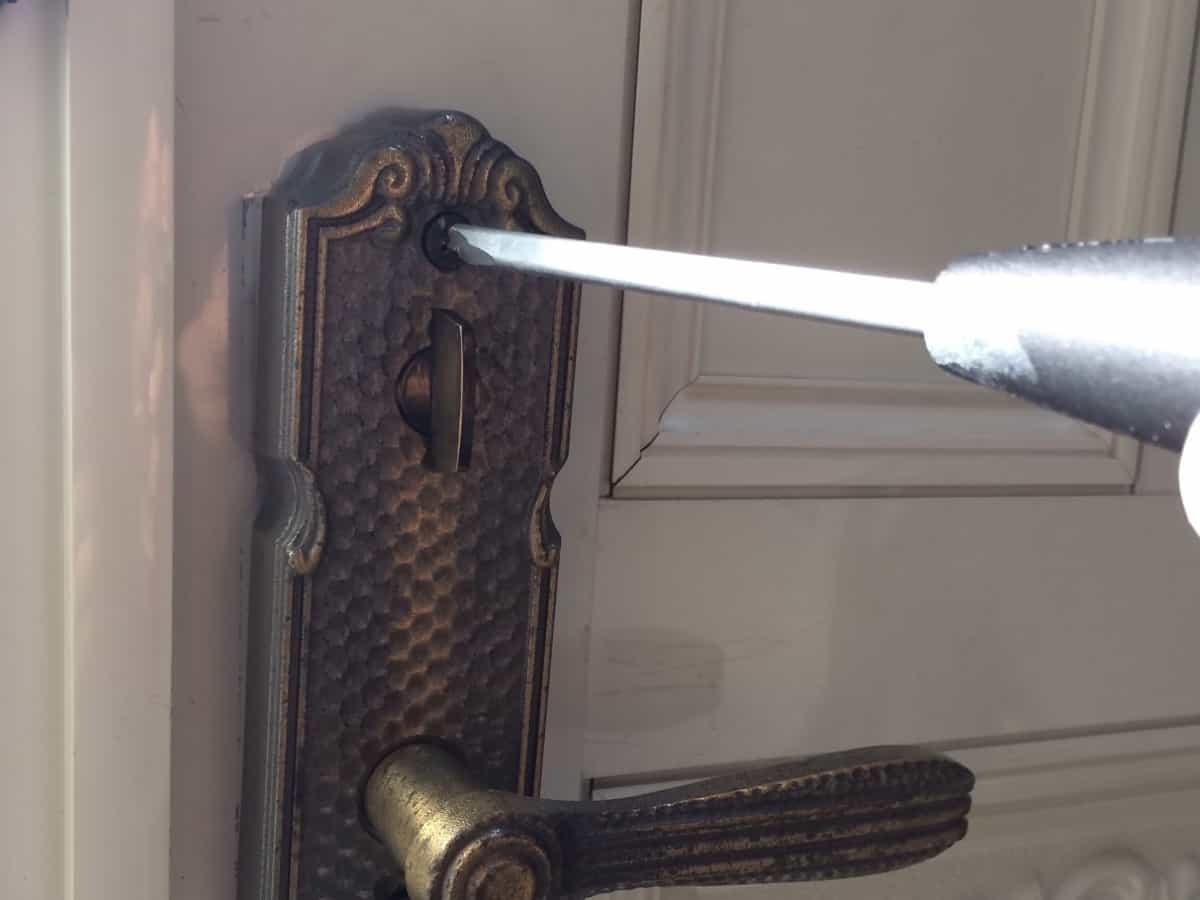 玄関扉のドアノブのネジを取り外す様子