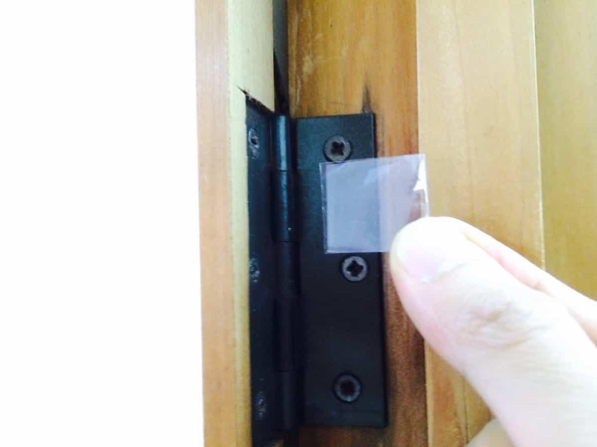 建付けの悪いドアの丁番の裏に薄板を挟む