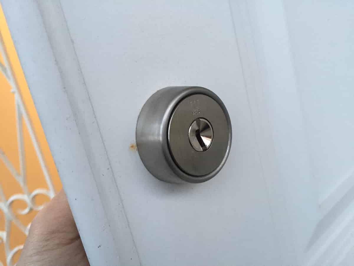 新しい補助錠の鍵シリンダーを玄関扉にはめ込む様子