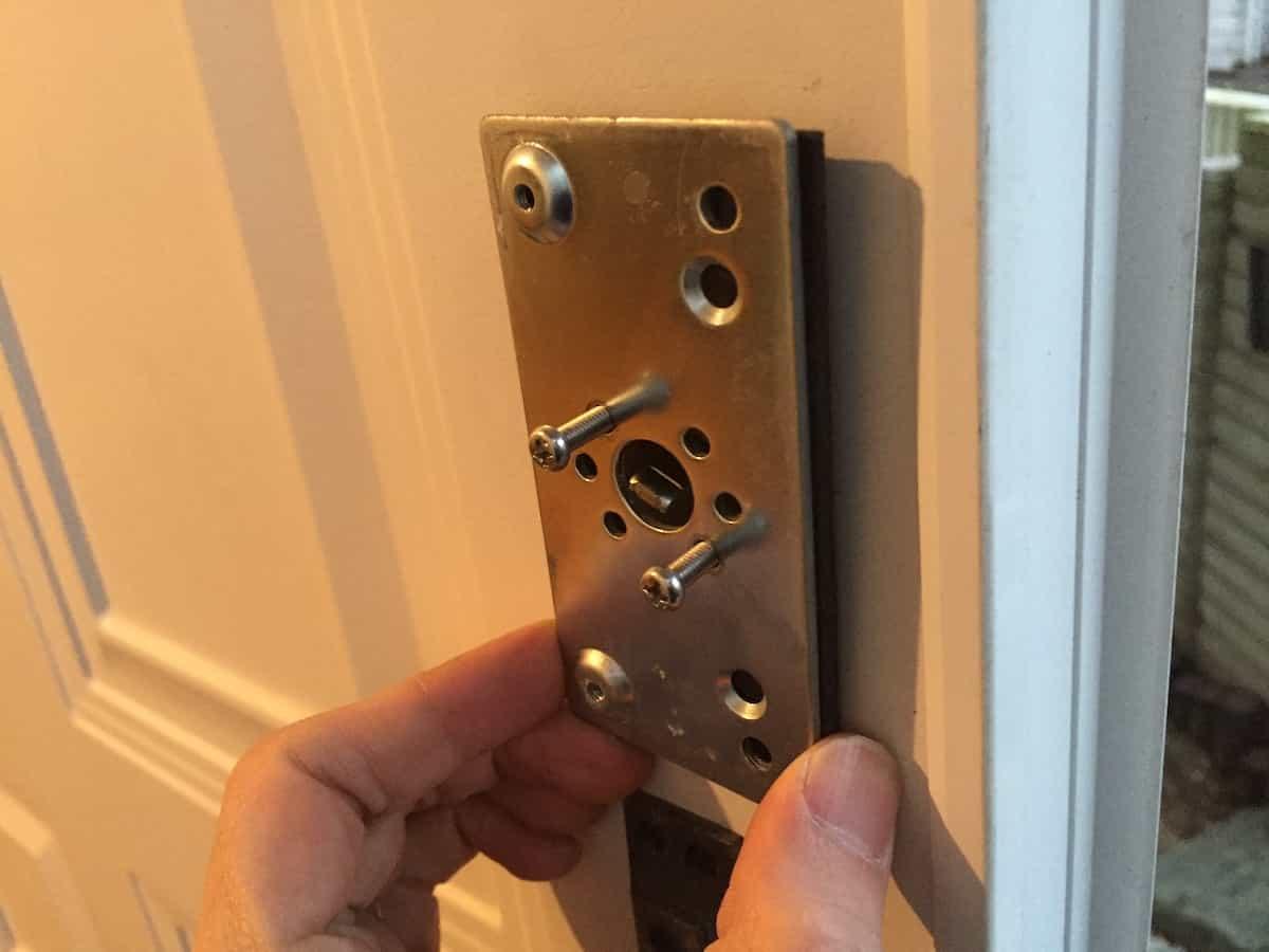 玄関扉に補助錠の土台プレートを取り付ける様子