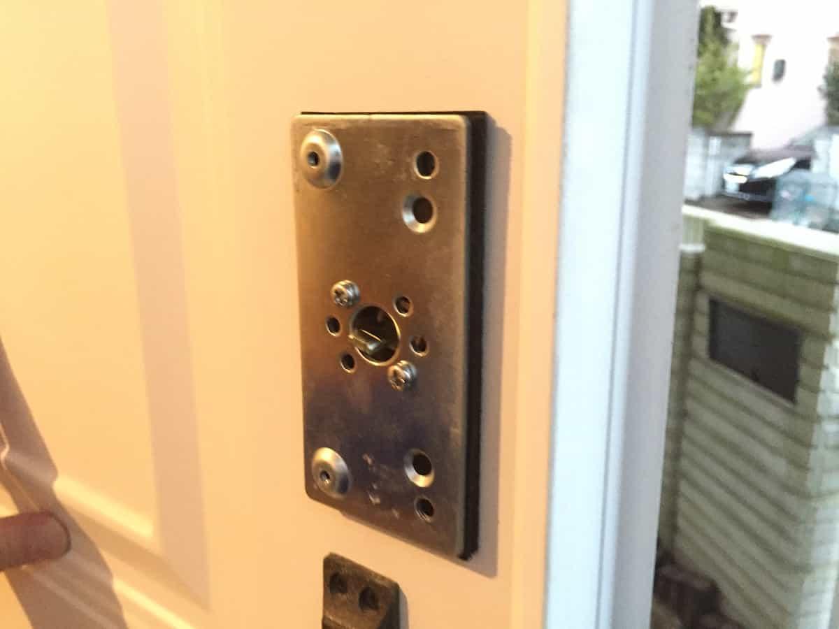 玄関扉に補助錠の土台プレートを取り付けた様子