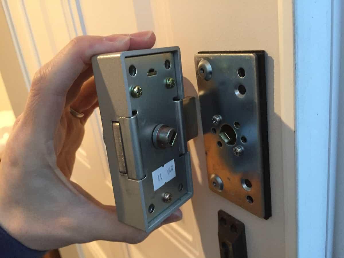 新しい補助錠を玄関扉に取り付ける様子