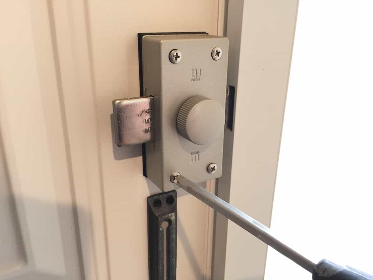 玄関扉の古い補助錠のネジを取り外す様子