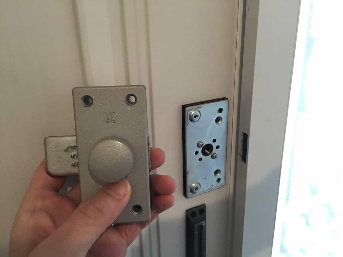 玄関扉の古い補助錠のネジを取り外した様子