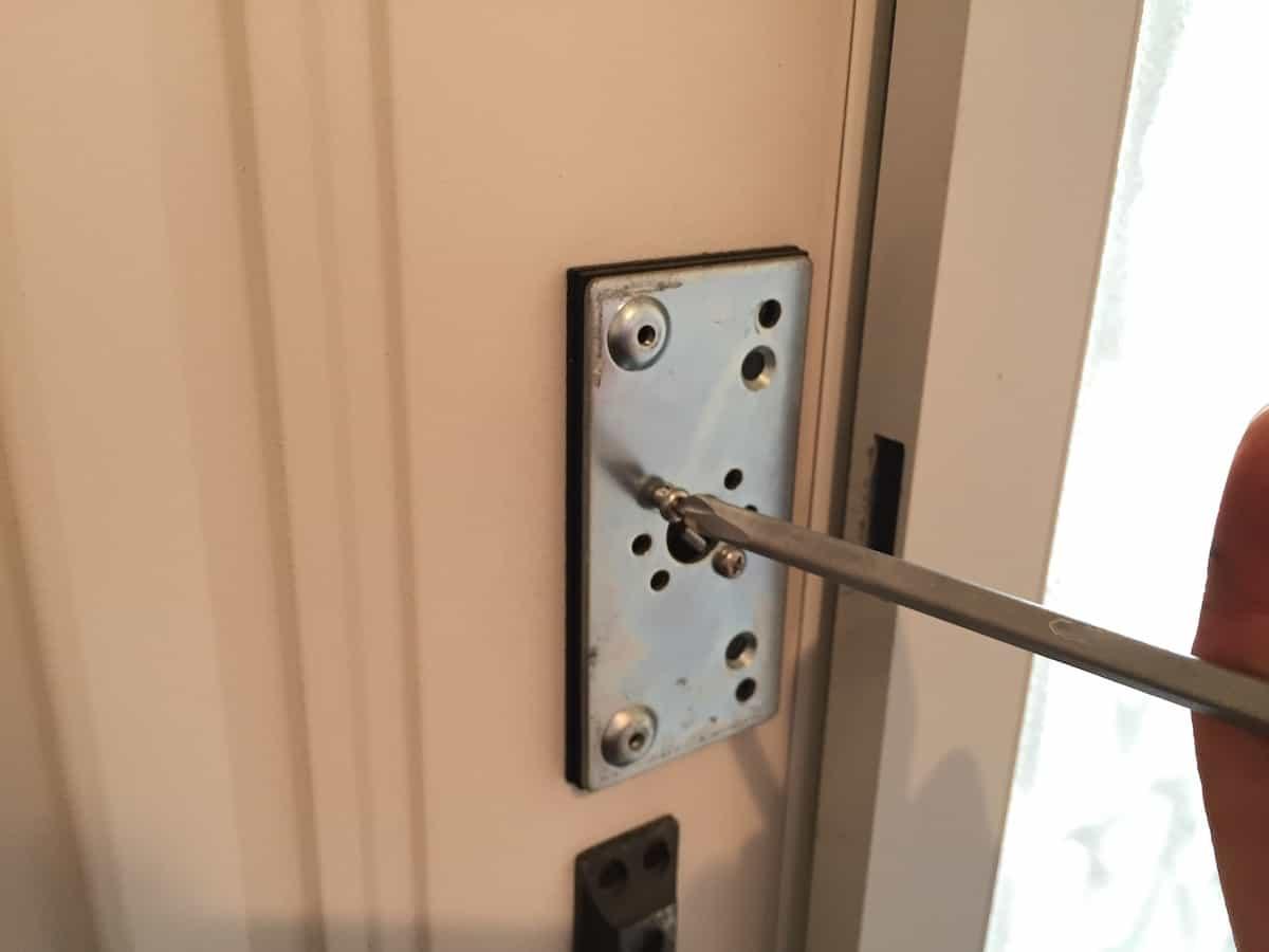 玄関扉の古い補助錠の土台プレートを取り外す様子
