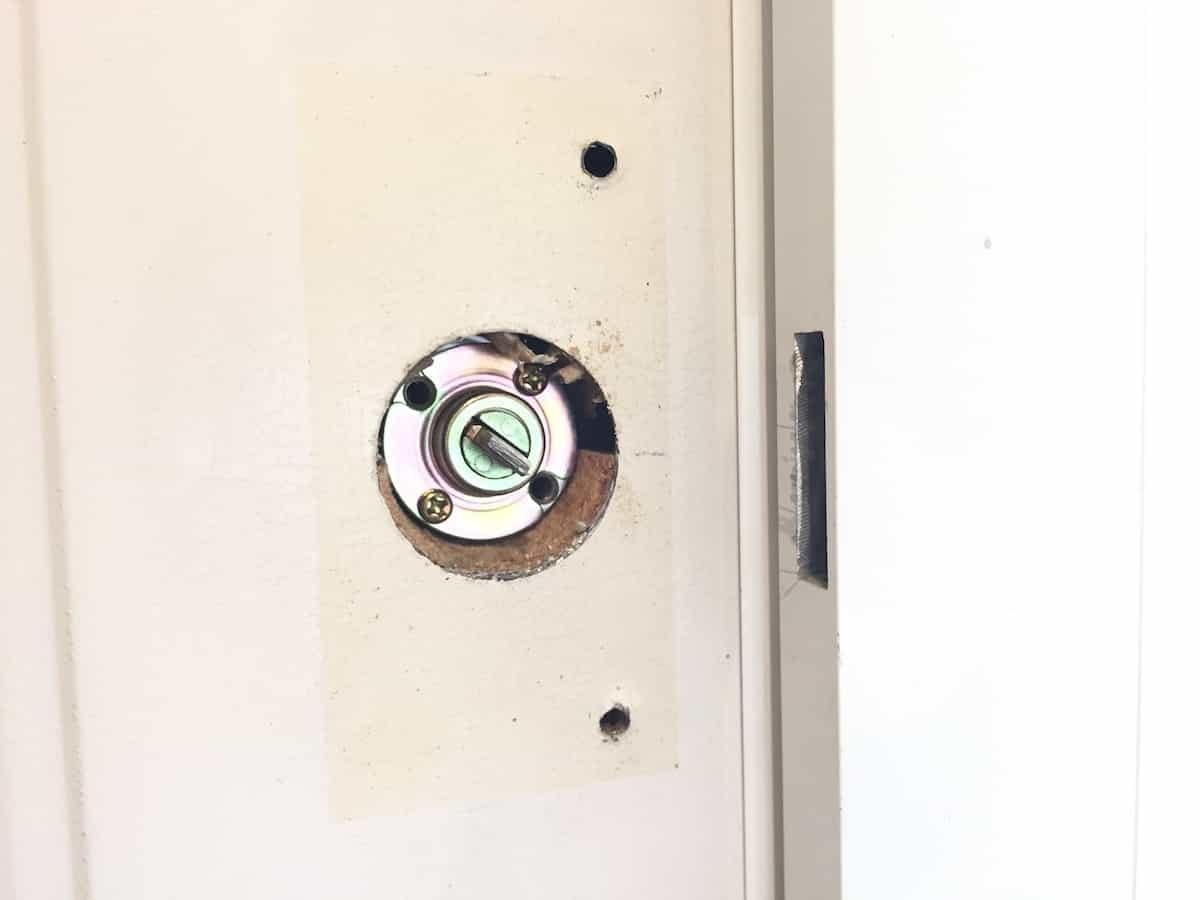玄関扉の古い補助錠の土台プレートを取り外した様子