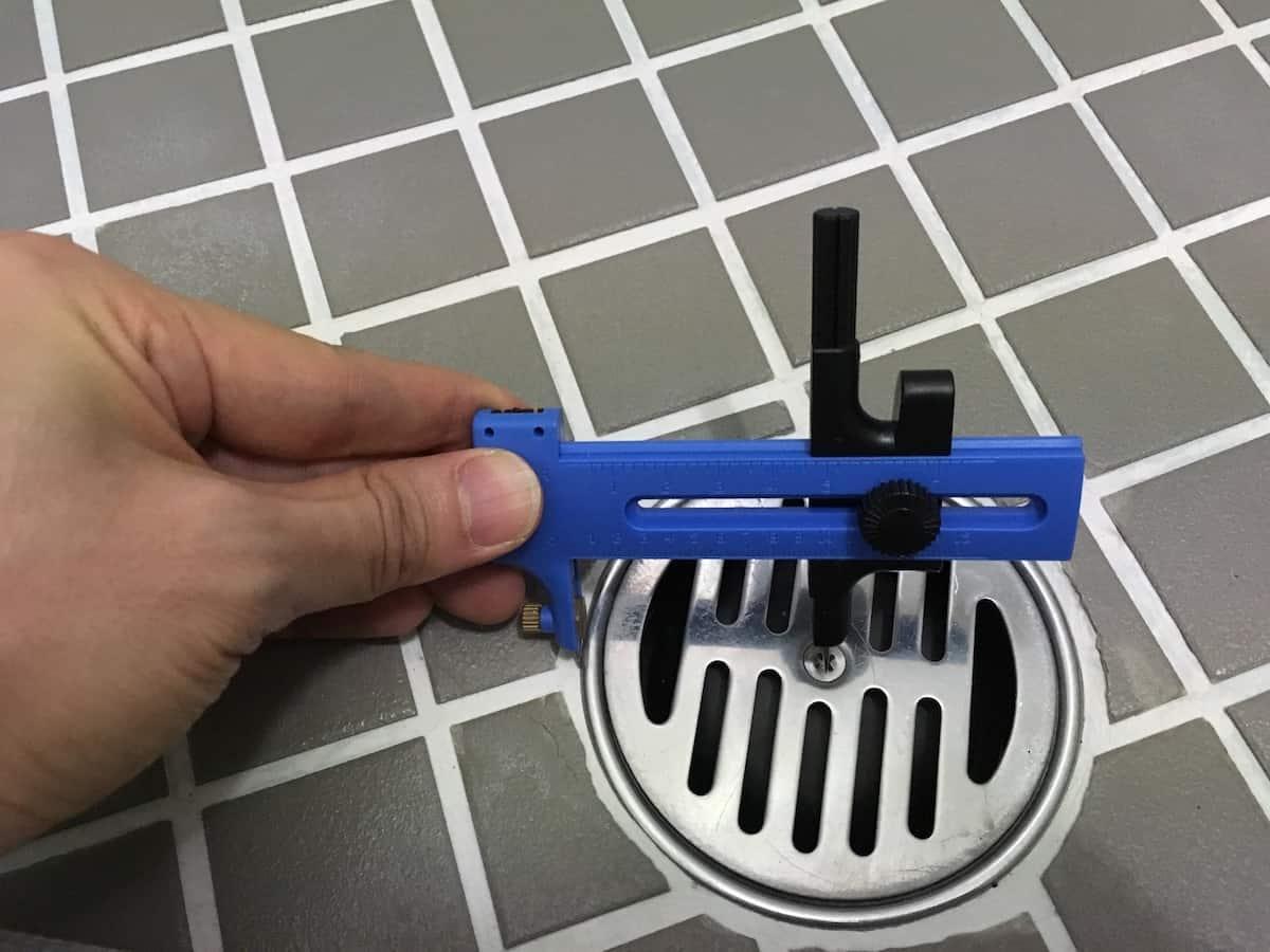 コンパスカッターで排水口の半径を測る様子