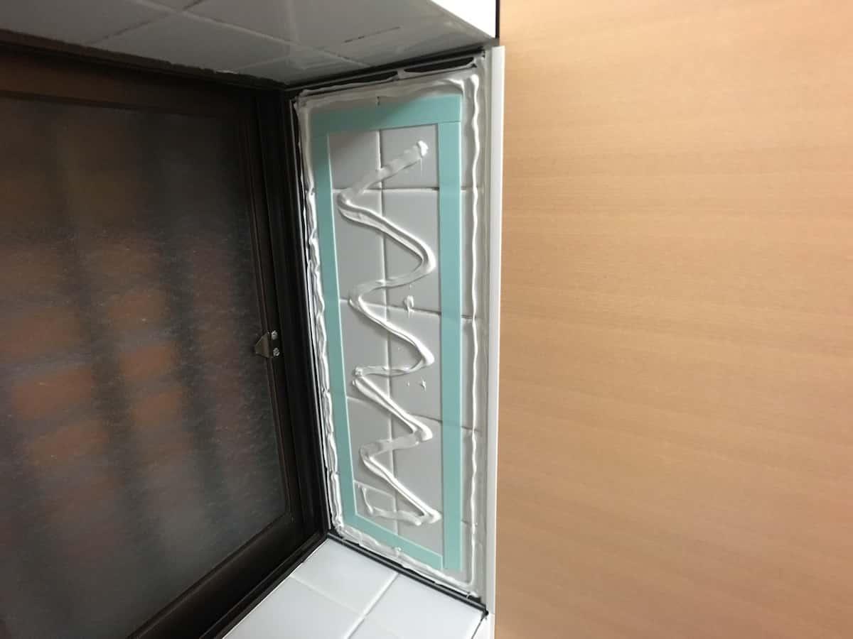 出窓部分にバスパネル「アルパレージ」を貼り付けるために両面テープと接着剤を塗る