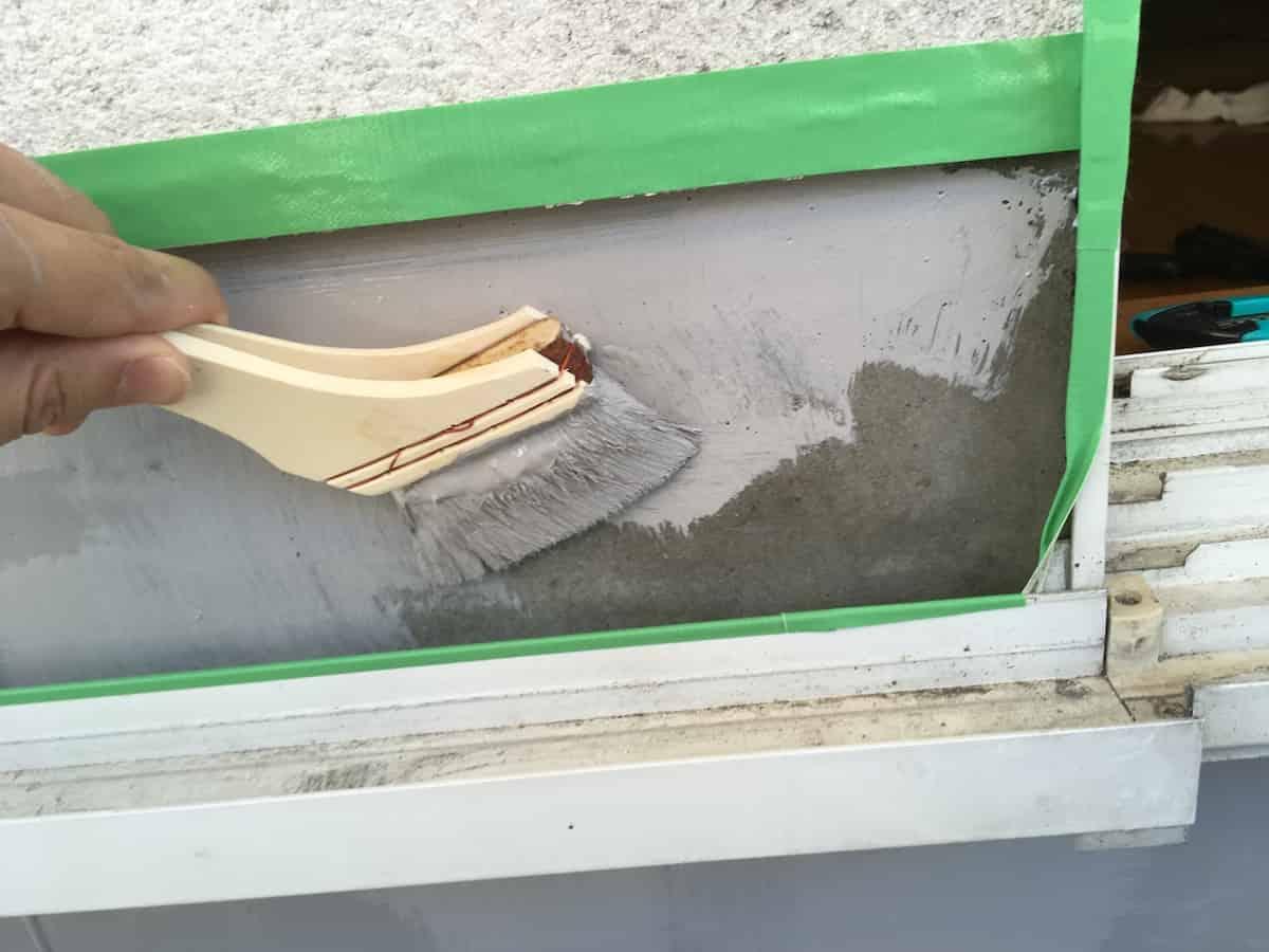 ベランダのセメント床に防水塗料を刷毛で塗る様子