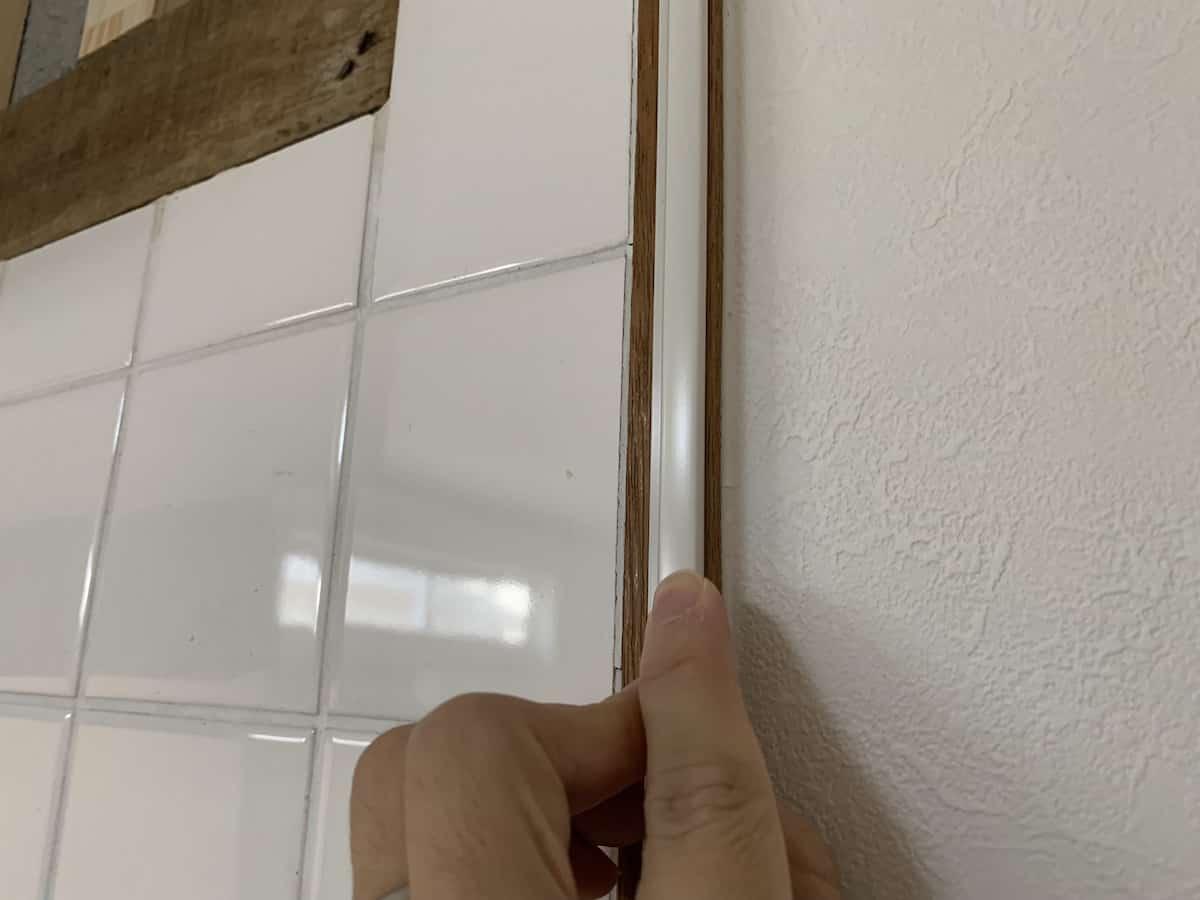 アイカ工業のキッチンパネル「セラール」の見切り材を貼り付ける様子