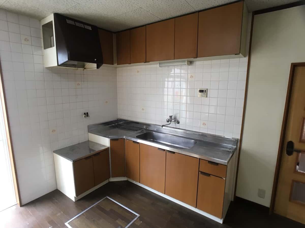 交換リフォーム前の古いセクショナルキッチン(流し台・ガス台・調理台・吊戸棚)
