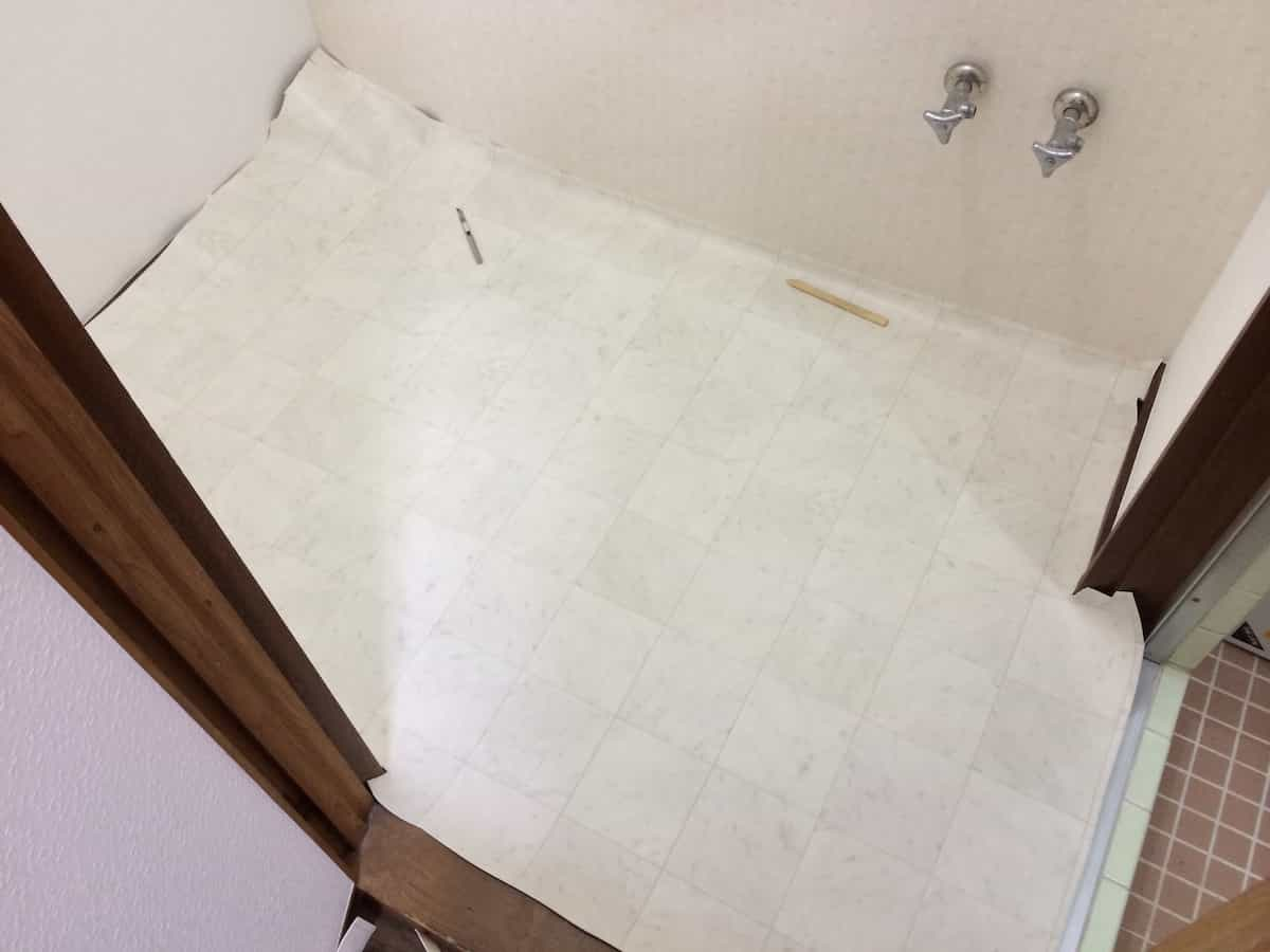 新しいクッションフロア(CF・床シート)を洗面所の床に合わせてカットする様子