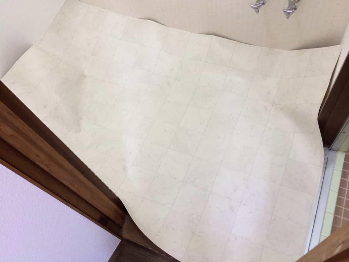 新しいクッションフロア(CF・床シート)を洗面所の床に広げる