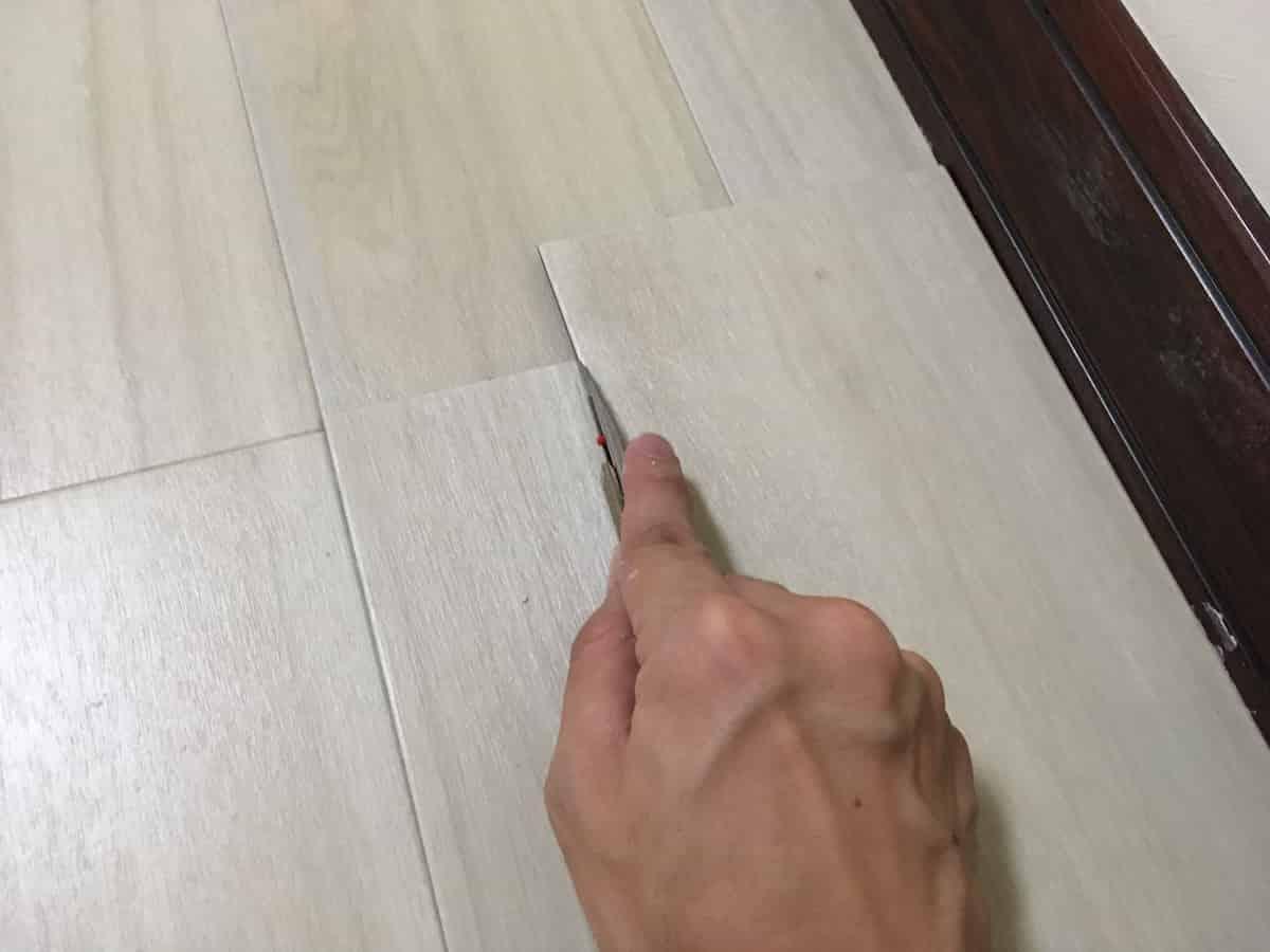 フロアタイル(塩ビタイル・プリントタイル)をカッターナイフで切っている様子