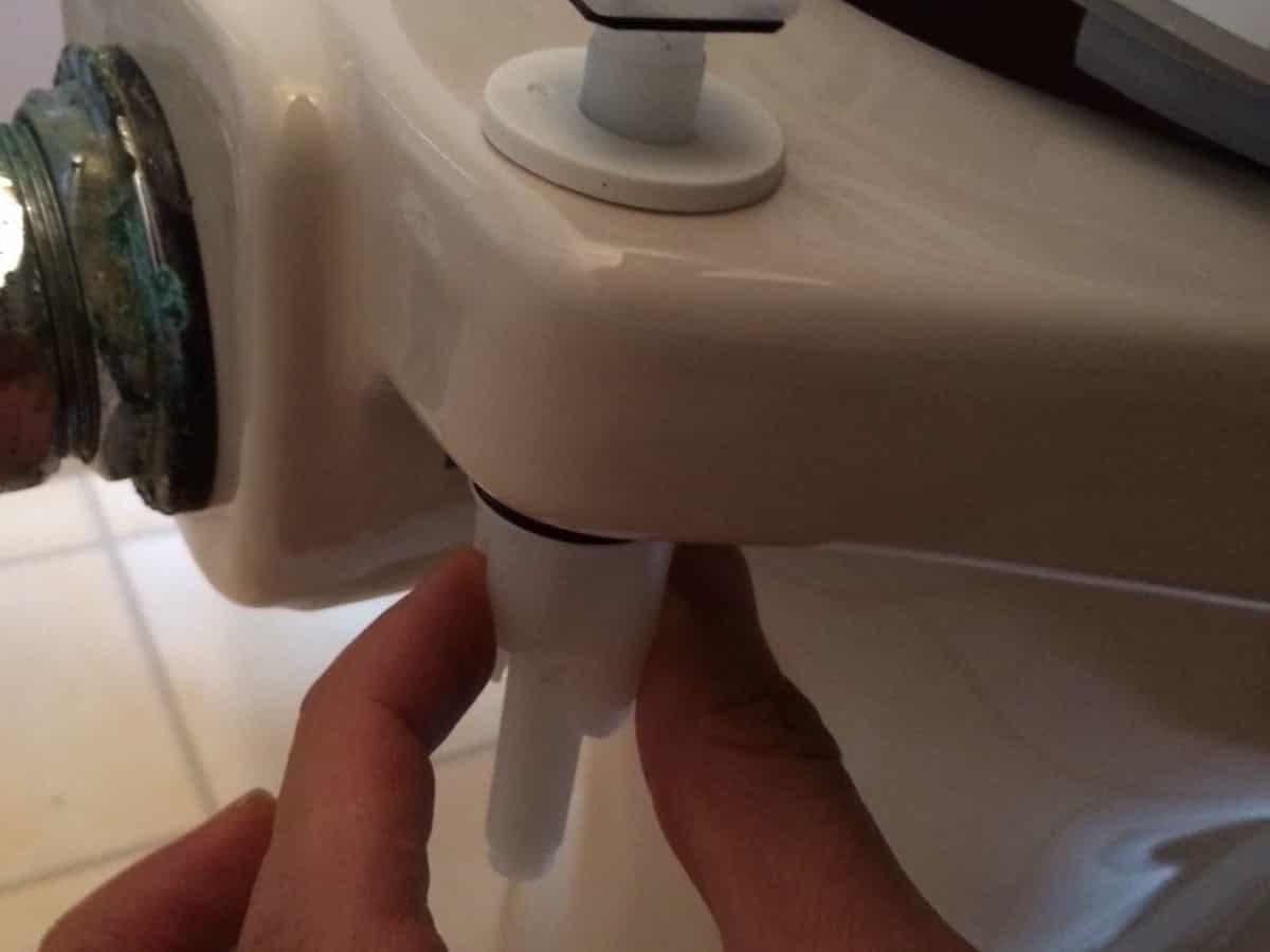 温水洗浄便座の便座固定用部品を便器に固定する様子