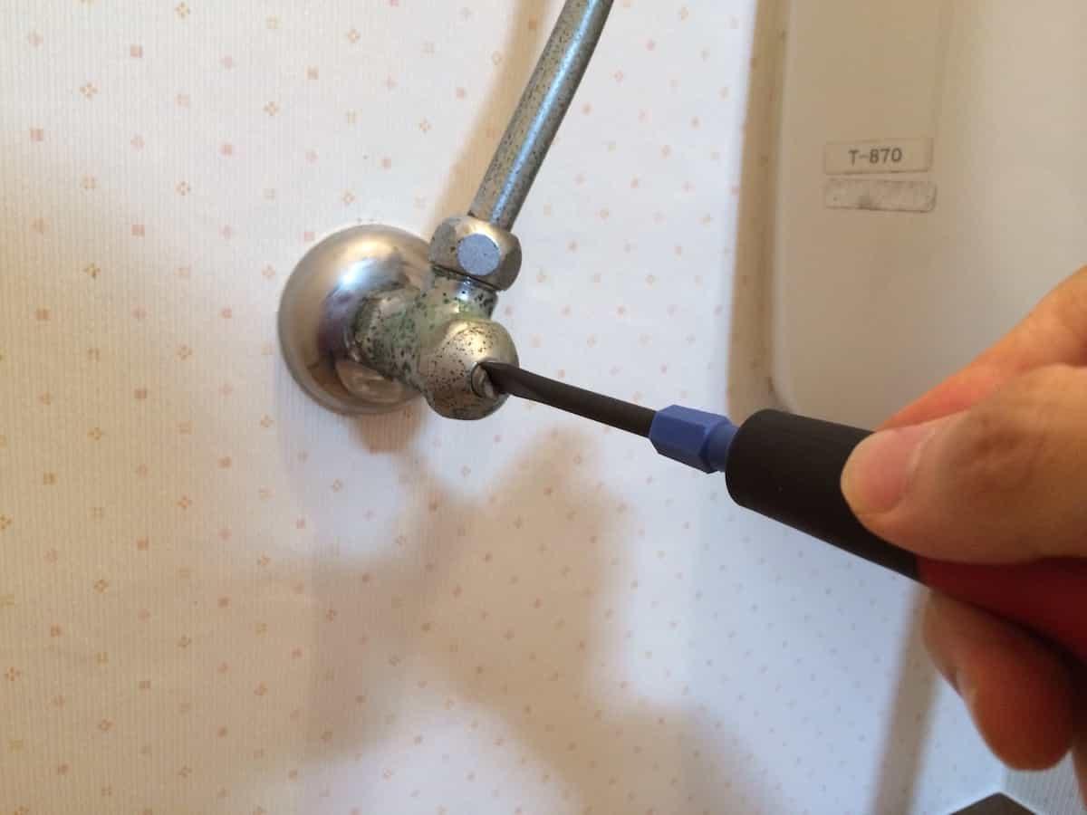 トイレの水道の元栓を締めている様子