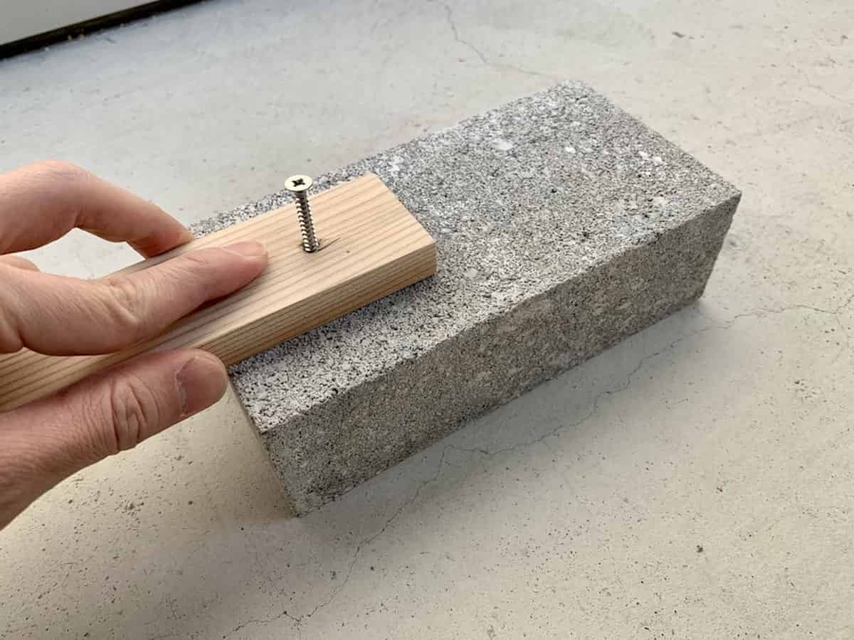 コンクリートブロックにネジ止めするためにネジを準備した様子