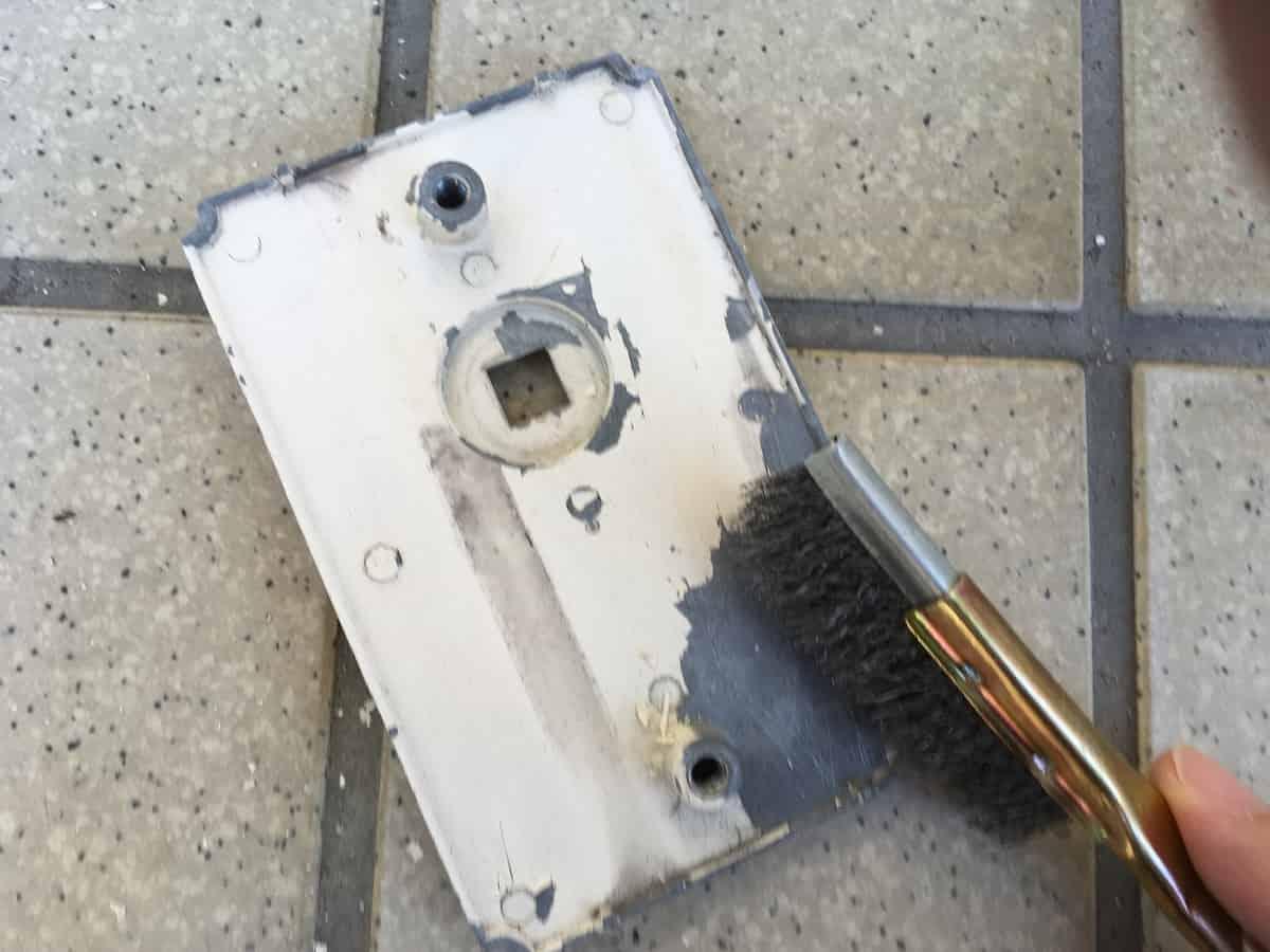 ワイヤーブラシで門扉の古いペンキ塗膜を取り除く様子