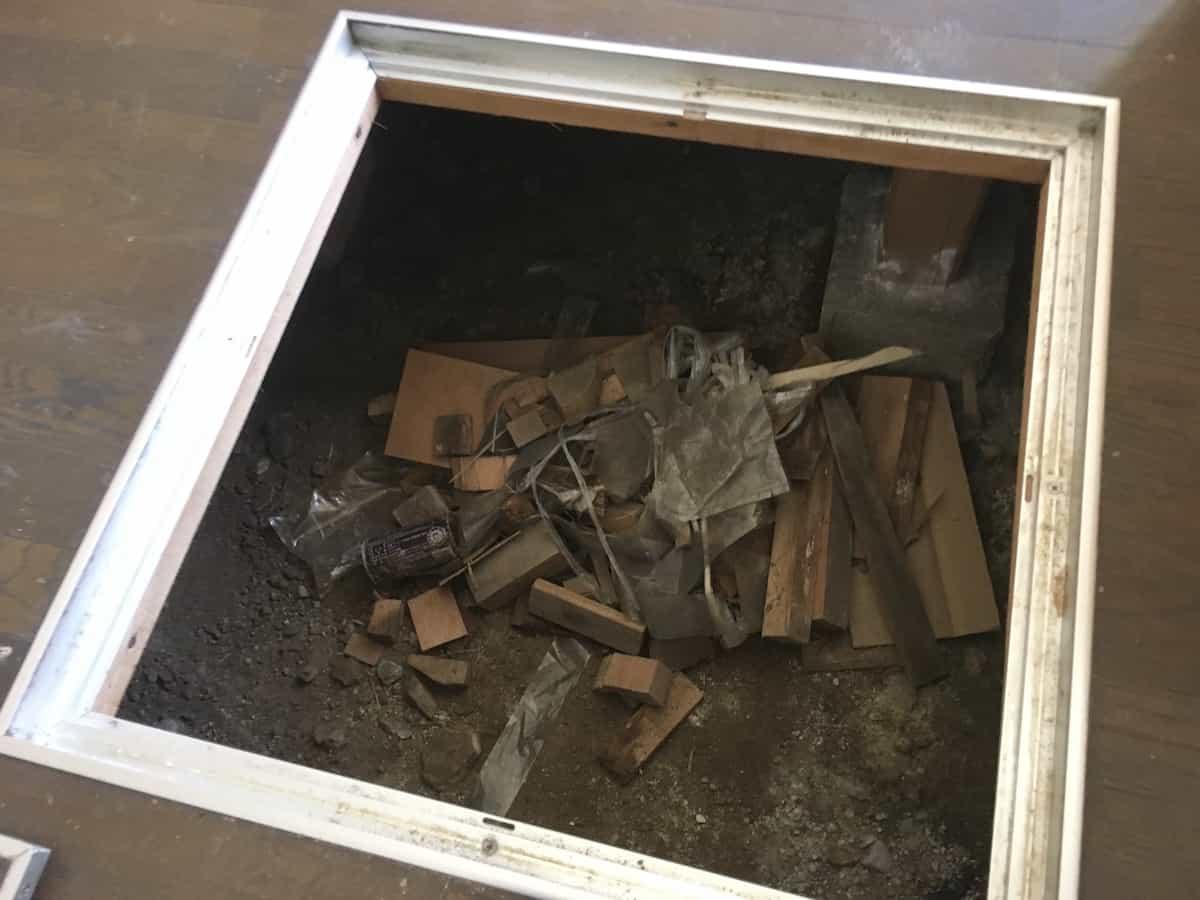床下に放置されていた木材や空き缶などのゴミ
