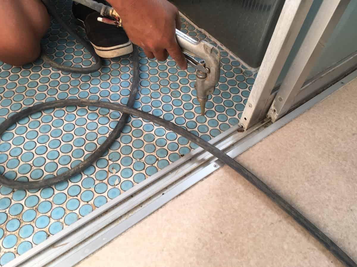 お風呂場のタイル床の下にシロアリ駆除の薬剤を注入