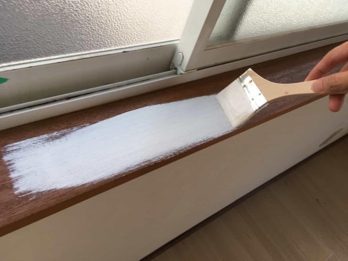 水性ペンキを窓枠木部に塗っている様子